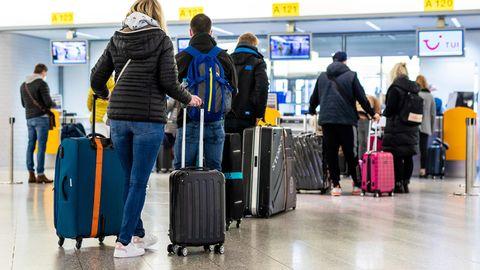 Reisende stehen vor der Gepäckaufgabe des Flughafens Hannover.