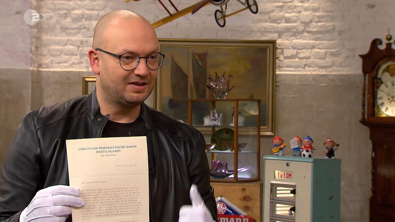 Sven Deutschmanek hält im Studio von Bares für Rares den Brief Adenauers in die Kamera