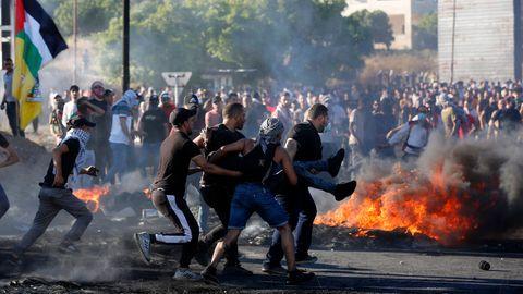 Männer tragen inmitten von Krawallen einen Mann, im Hintergrund ist ein Feuer zu sehen