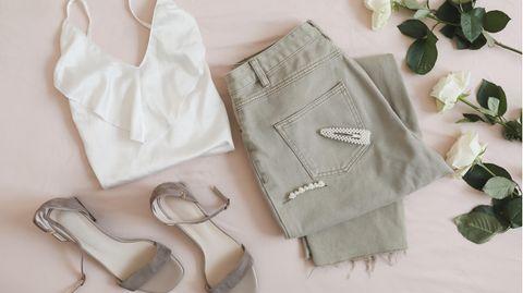Lingerie-Top und Jeans liegen drapiert auf dem Boden