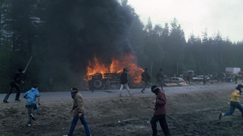 Ein Mannschaftswagen der Polizei brennt, davor laufen vermummte Demonstranten umher