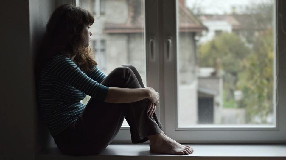 Junge Frau sitzt traurig am Fenster