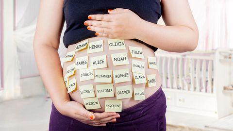 Eine Schwangere hat Post-Its auf ihren Bauch geklebt, auf denen viele verschiedene Namen stehen