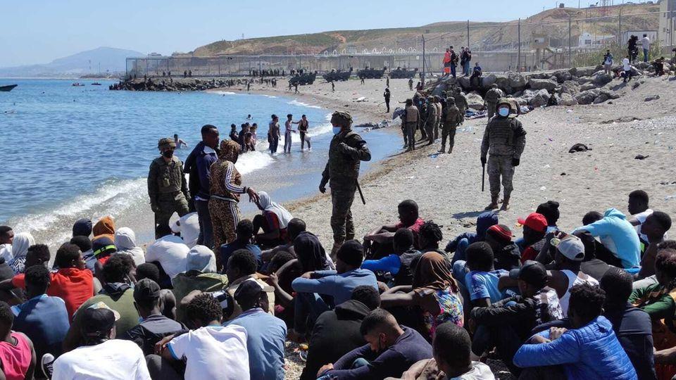 Die Migranten werden vom spanischen Militär bewacht.