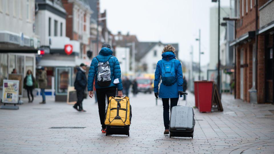 Urlauber gehen mit ihren Koffern durch die Fußgängerzone in Richtung Bahnhof