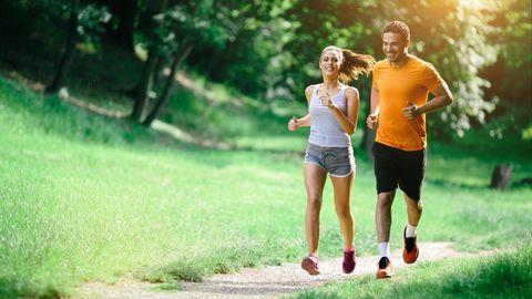 Jogging Outfit: Junge Frau und junger Mann joggen bei Sonnenschein im Park