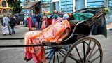 Indien, Kolkata: Eine an Covid-19 erkrankte Frau wird auf einer Rikscha zum Krankenhaus gebracht