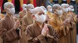 Buddhistische Mönche und Nonnen, die wegen der Corona-Krise einen Mund-Nasen-Schutz tragen, beten gemeinsam