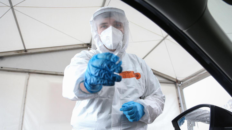 Test auf das Coronavirus: Ein Mitarbeiter einer Drive-In-Teststation nimmt einen Abstrich