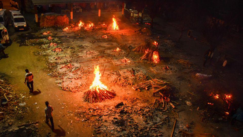 Vielerorts ist die Lage in dem 1,3-Milliarden-Einwohner-Land längst außer Kontrolle. Hier in Neu Delhi lodern Holzfeuer auf dem Gelände eines Krematoriums, in dem Opfer einer Covid-19 Erkrankung verbrannt werden.