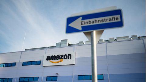 Ein Einbahnstraßenschild ist vor einem Amazon-Schriftzug zu sehen.