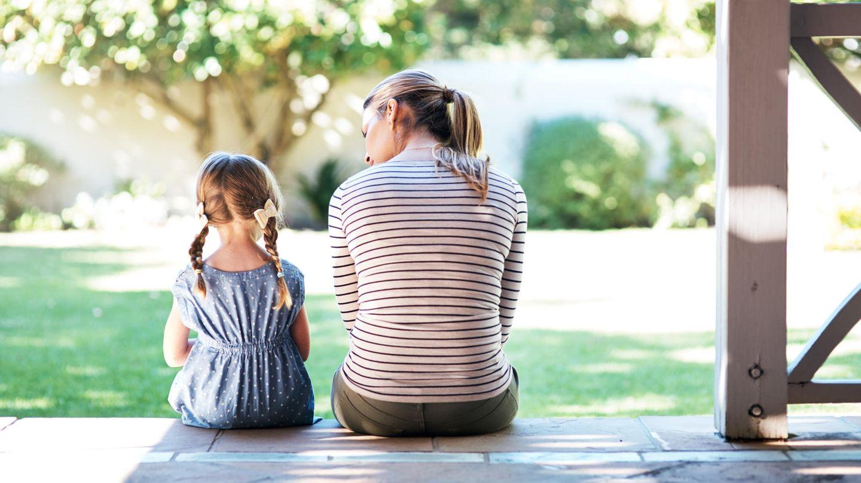 Mutter und Tochter sitzen auf Treppen einer Veranda und unterhalten sich