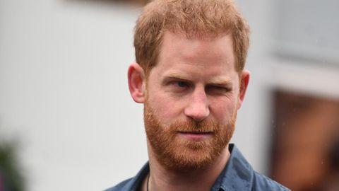 Prinz Harry trägt ein blaues Hemd und blickt ernst