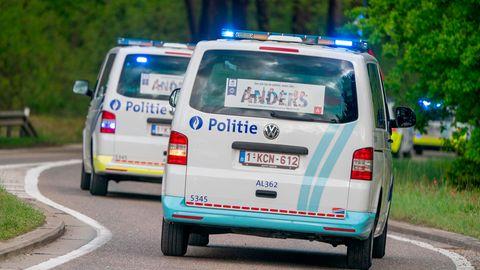 Zwei Polizeitransporter fahren durch ein Waldstück
