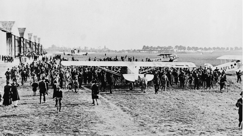 """21. Mai 1927: Charles Lindbergh landet nach mehr als 33 Stunden Transatlantik-Flug in Paris  Personaldes FlughafensLe Bourget in Paris rollen die """"Spirit Of St. Louis""""desamerikanischen Piloten CharlesLindbergh auf den Flugplatz, nachdem sie am 21. Mai 1927 von begeisterten Lindbergh-Anhängern in beschädigt worden war. Mehrere Polizisten sind nötig,um dieZuschauer unter Kontrolle zu halten.  Lindbergh flog als erster Mensch der Welt alleine in einem Nonstop-Flug über den Atlantik. Am 20. Mai 1927 starteter in New York in den USA. Nach 33 Stunden erreichter Paris, wo er von Menschenmassen gefeiert wird. Lindbergh wird über Nacht zum Helden – auf beiden Seiten des Atlantiks. Lindberghs Flug mit der """"Spirit Of St. Louis"""" ist allerdings– entgegen der häufigen Annahme– nicht der erste Überflug über den Großen Teich: Schon 1919 wagenJohn Alcock und Arthur Whitten Brown die Überquerung von Kanada nach Irland. Sie brauchen dafür mehr als 16 Stunden."""