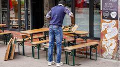 Ein Mitarbeiter eines Restaurants stellt im Hamburger Schanzenviertel Tische und Bänke auf