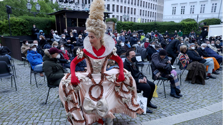 """Nach monatelanger Zwangspause wurde am Deutschen Theater in Berlin wieder eine Premiere vor Publikum aufgeführt. """"Tartuffe oder Das Schwein der Weisen"""" stand am Samstagabend auf dem Programm - das Publikum wickelte sich auf dem Vorplatz in Regenjacken und Decken."""