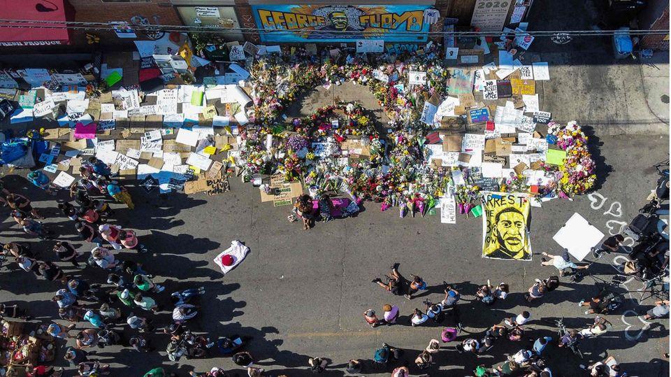 Menschen versammeln sich an einer Gedenkstelle für George Floyd