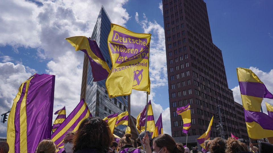 """Bei einer Demonstration gegen steigende Mieten halten Teilnehmer Fahnen der Initiative """"Deutsche Wohnen & Co. enteignen"""" in die Höhe"""