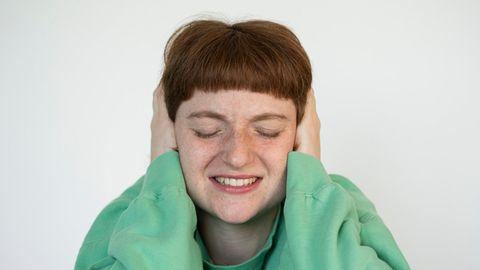 Frau hält sich beide Ohren zu
