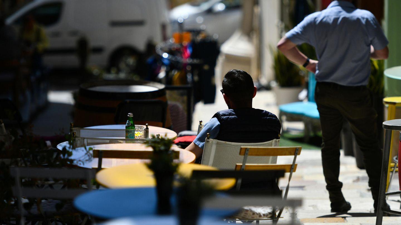 Menschen sitzen bei Sonne in einem Straßencafé