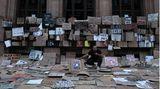 """Ein Mann sitzt in einem Schildermeer nach einem Protestzug der """"Black Lives Matter""""-Bewegung"""