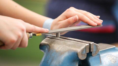 Die Hände einer jungen Frau führen eine Feile über ein in blauem Schraubstock eingespannten Metallstift