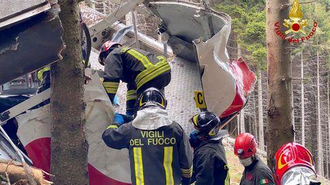 Feuerwehrmänner inspizieren die zerstörte Gondel