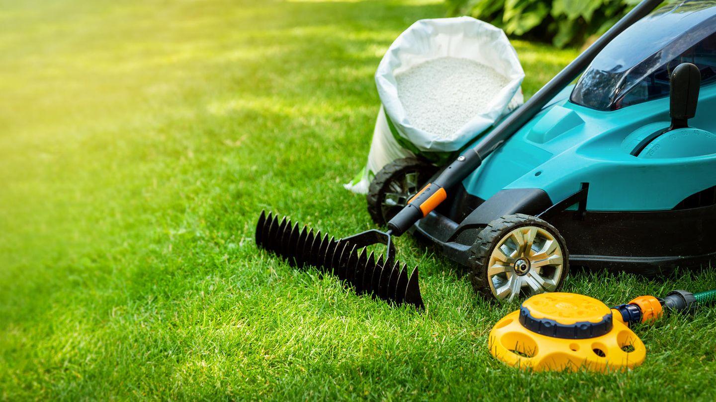 Rasen clever pflegen: Gartengeräte zur Rasenpflege stehen auf einer Wiese bereit