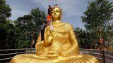 Bhopal, Indien.Ein buddhistischer Mönch klettert auf eine riesige Buddha-Statue, um sie am Vorabend von Buddha Purnima, einem Feiertag, der traditionell zu Buddhas Geburtstag gefeiert wird, auch bekannt als Vesak-Fest,zu waschen und zu schmücken.