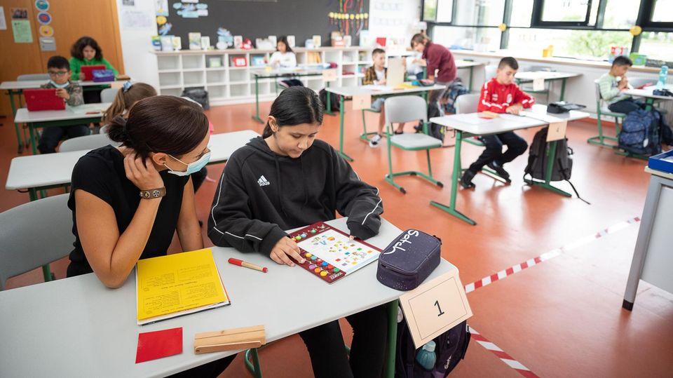 Lehrerin erklärt einer Schülerin die Aufgaben