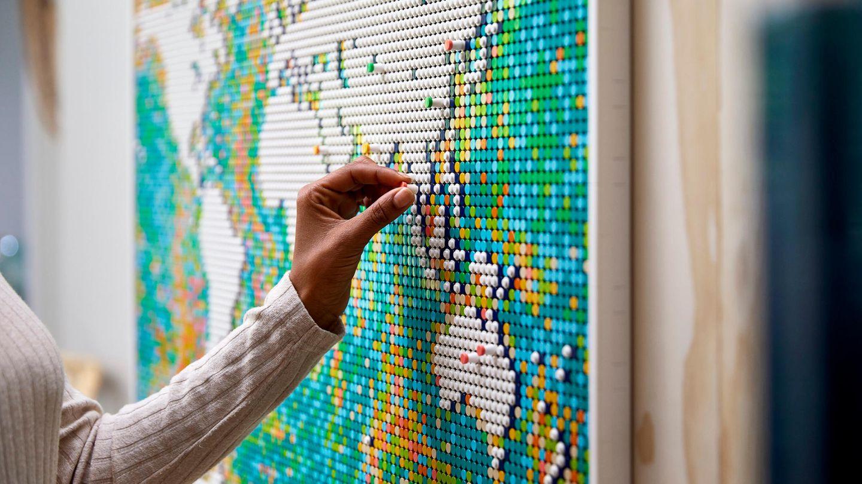 Lego World Map: Frauenhand steckt einen Pin auf die Lego Weltkarte