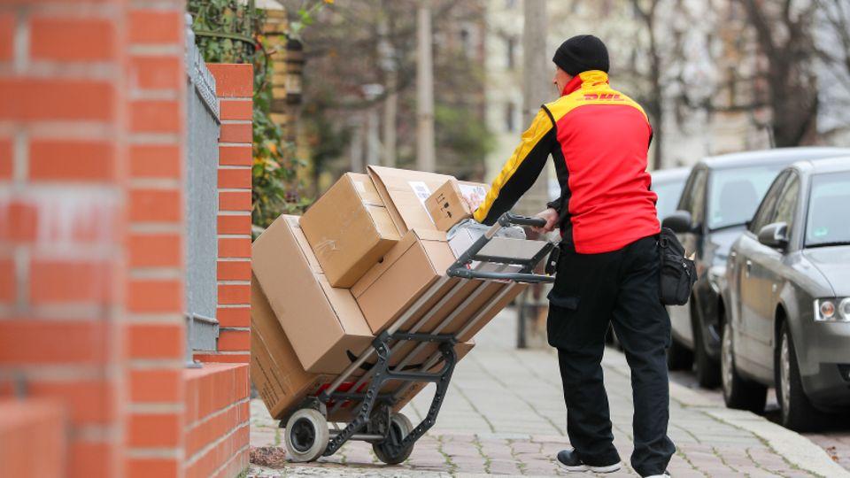 DHL-Zusteller mit einer Sackkarre voller Pakete.