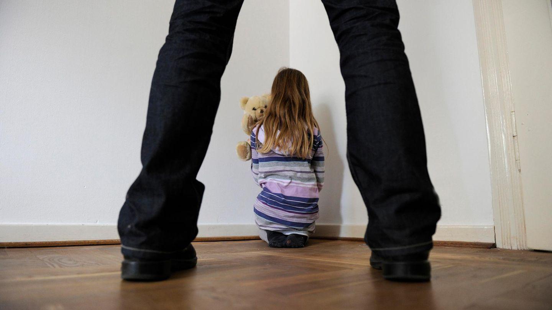 Ein Mann steht hinter einem Kind, das sich in einer Ecke verkrochen hat (Symbolbild)