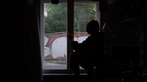 Ein Kind sitzt während des Corona Lockdowns am Fenster.