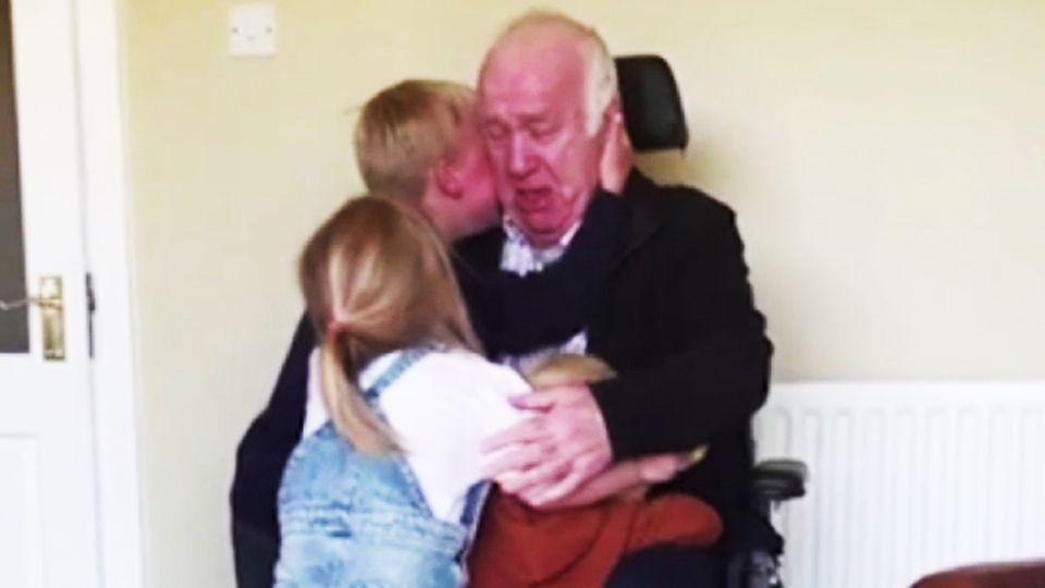 Drei Kinder umarmen ihren Großvater