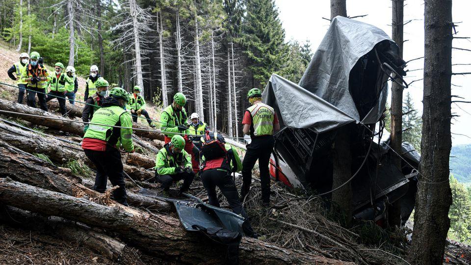 Am Rande einer Lichtung in einem Bergwald stehen Rettungskräfte in neongrünen Helmen und Jacken vor den Trümmern einer Gondel