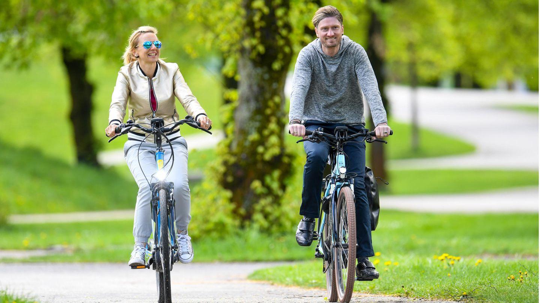 Ein Paar fährt auf E-Bikes durch einen Park