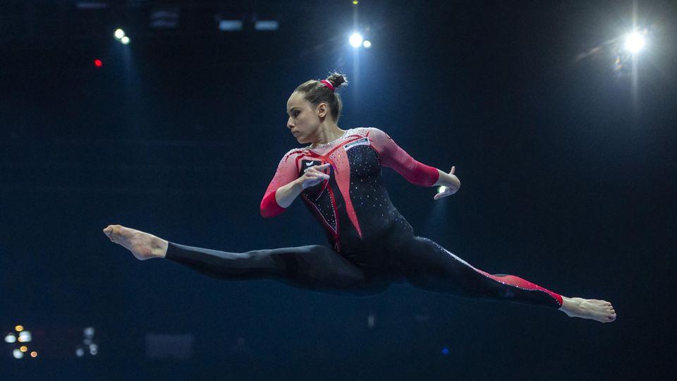 Turnerin Sarah Voss springt im Spagatsprung auf dem Balken und trägt dabei einen langen Anzug