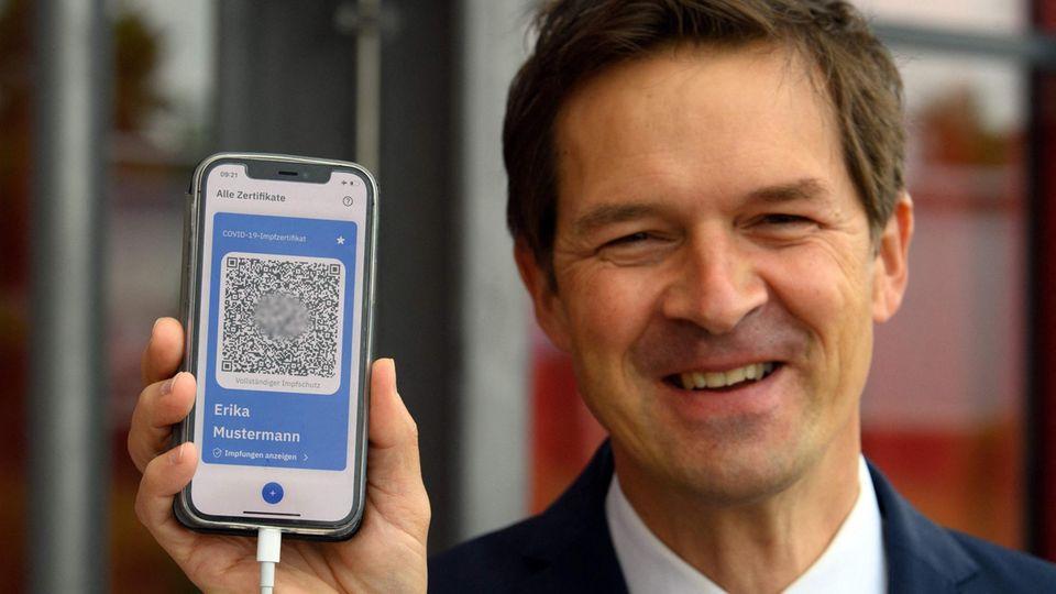 Ein weißer Mann im blauen Jackett lächelt, während er ein Smartphone-Display mit blau umrandetem QR-Code hochhält