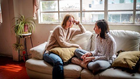 Mutter und Tochter sitzen auf der Couch und unterhalten sich