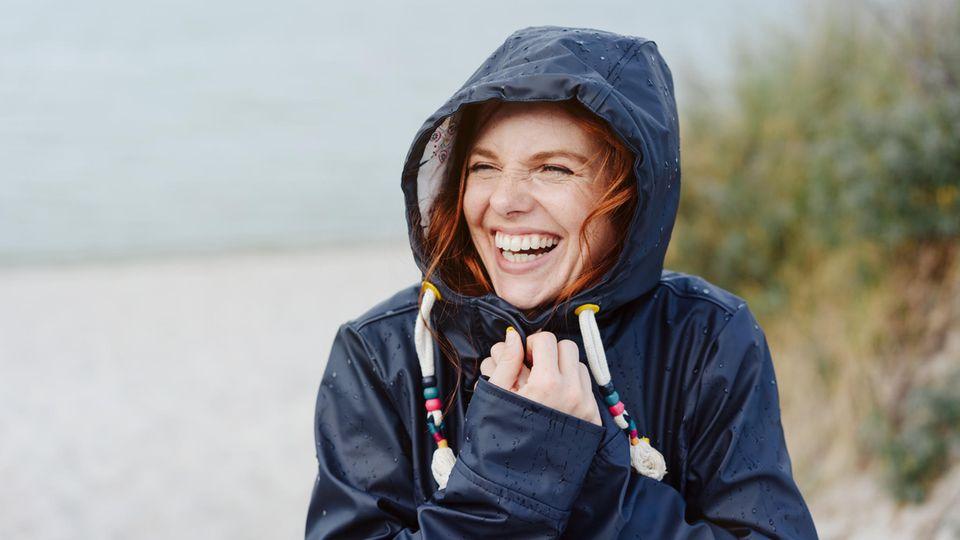 Lachende Frau mit roten Haaren im Regenmantel vor dem Meer