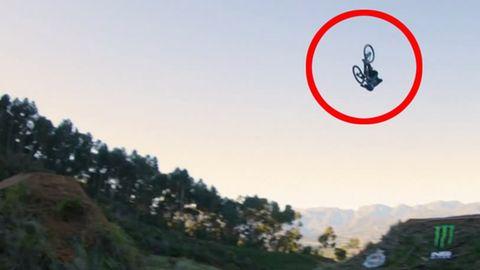 Hoch über einem Erdwall zwischen Bäumen fliegt ein Mountainbiker kopfüber mit seinem Rad über sich
