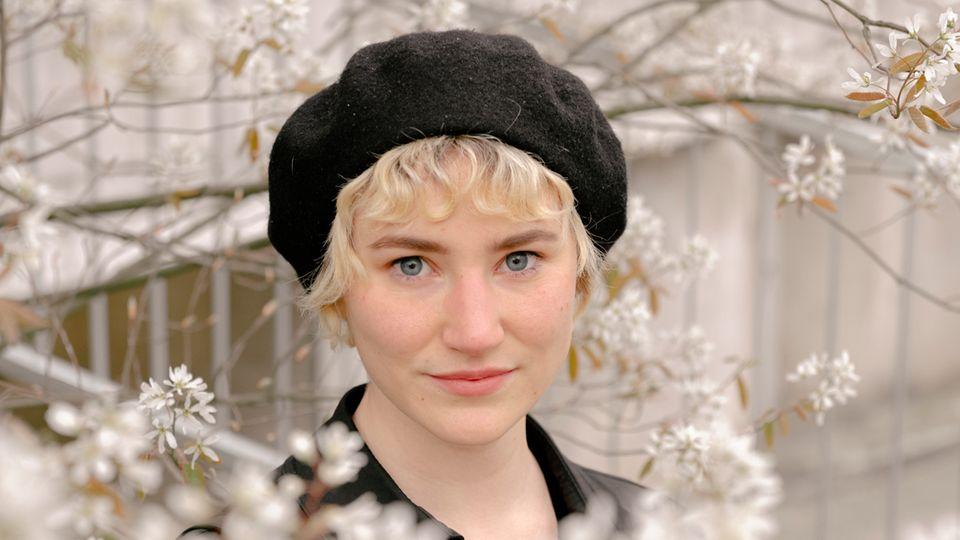 Sophia Sailer hat kurze blonde Haare und posiert hinter Blumen