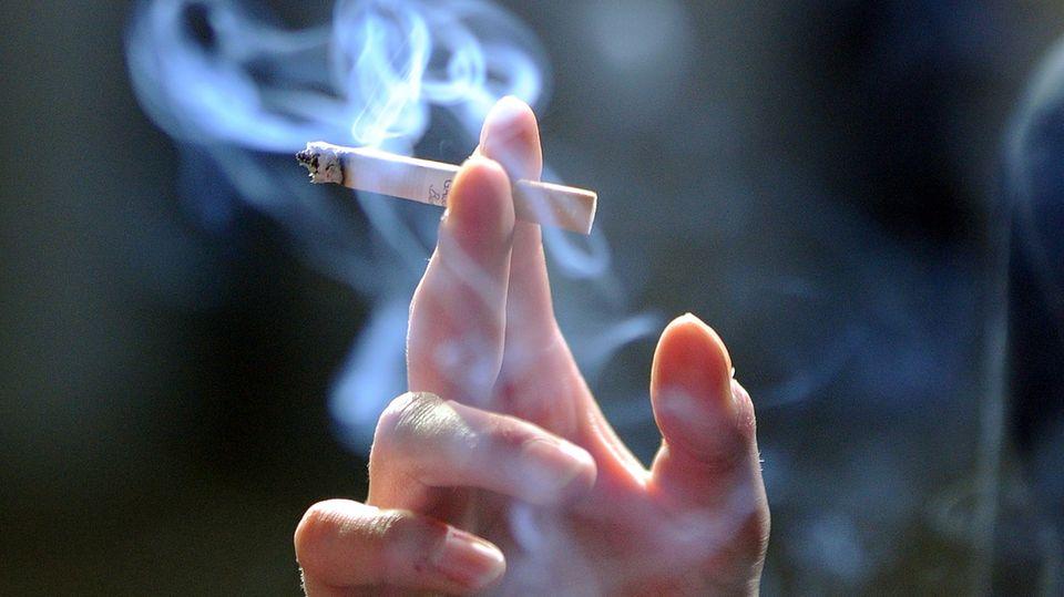 Eine Hand hält eine qualmende Zigarette
