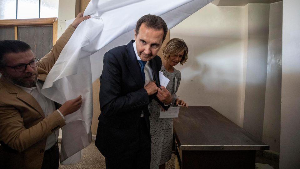 Baschar al-Assad (M.), Präsident von Syrien, und seine Frau Asma (r.) geben ihre Stimmen ab