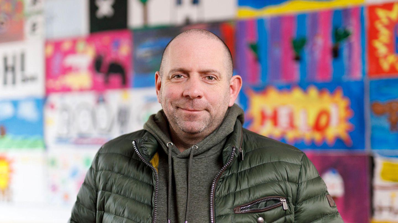 Matthias Distel aka Ikke Hüftgold steht vor einer bunten Wand