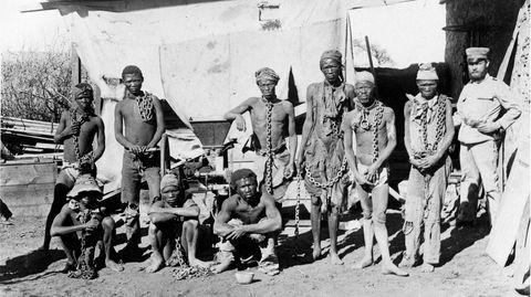 Ein Schwarz-Weiß-Foto zeigt einen mutmaßlich deutschen Uniformierten, der in Ketten gelegte Schwarze bewacht