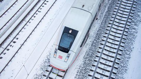 Ein ICE 4 fährt auf einem verschneiten Gleis
