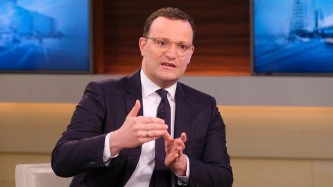 Ein Mann mit Brille und braunen Locken sitzt im Anzug in einem TV-Studio und gestikuliert mit beiden Händen vor der Brust